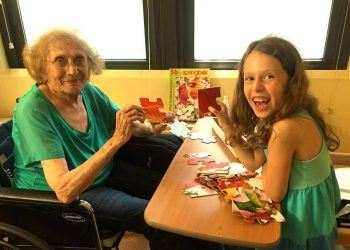 Hailey Richman, age 8, doing a puzzle with her Grandma (Courtesy of Kid Caregivers)