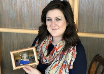 Leslie Tracy holds a photo of her mother. She was able to take family leave through her company, biotech manufacturer Promega, when her mother was dying from cancer. (Photo courtesy of Promega)