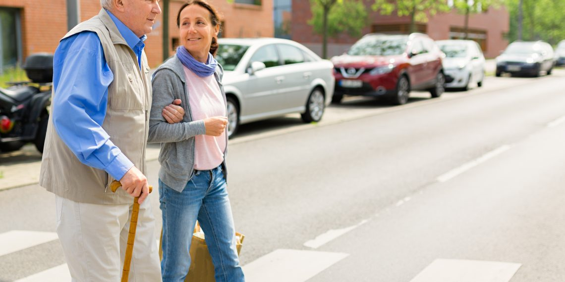 Senior woman and caregiver go walking outdoors, crosswalk