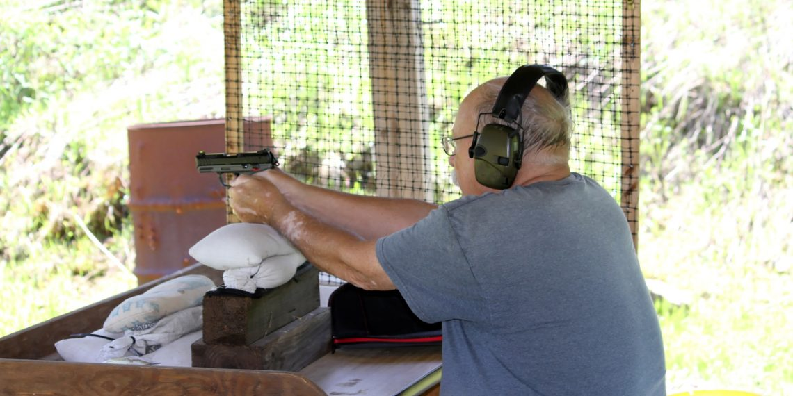 Senior Male aims a 22 at a target wearing ear and eye protection.