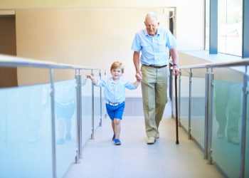 Boy helps his grandfather at a hospital. Young children are also caregivers that provide medical care