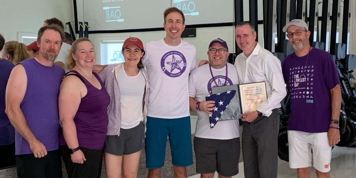 Rep. Brian Fitzpatrick, second from right, honors Phil Gutis, third from right, and members of his rowing club.