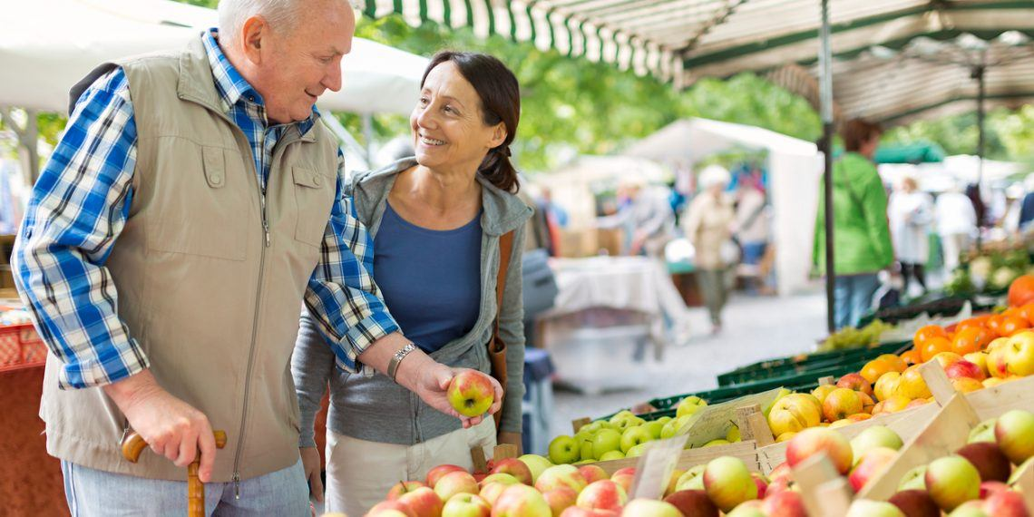 Senior man with caregiver shopping at market place